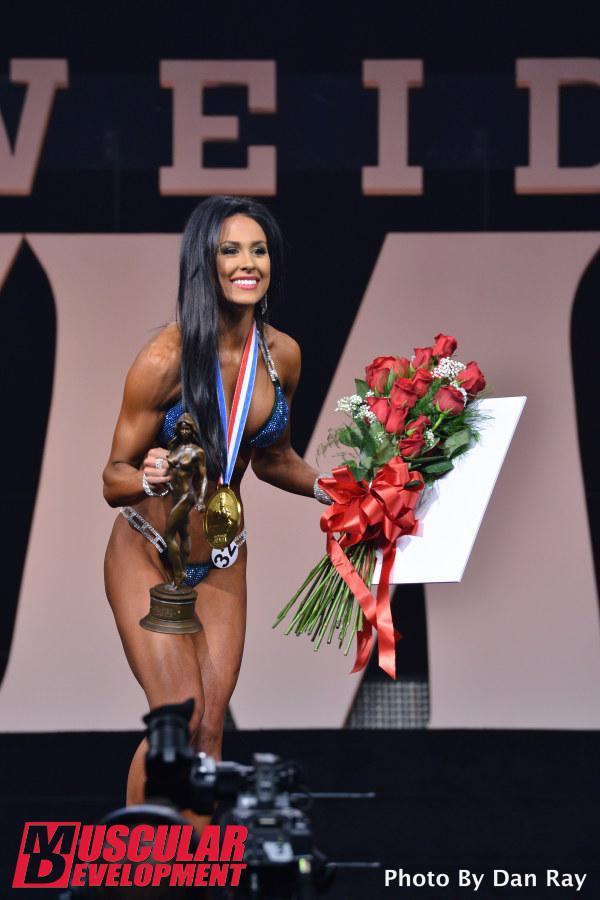 Ashley Kaltwasser, recibiendo el diploma, el trofeo y la medalla de ganadora de Bikini Olympia 2015